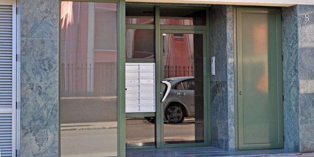Puerta de entrada de aluminio lacado y vidrio laminado con buzones incorporados